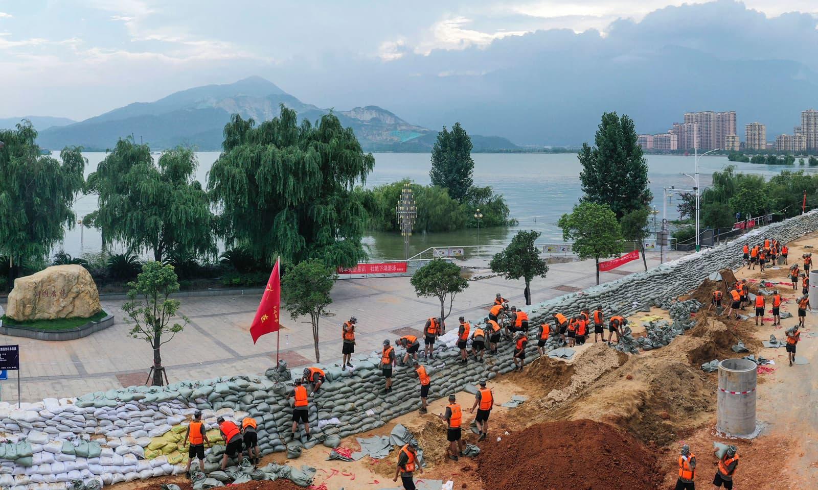 چین کے شہر لوشان میں ڈیم کی سطح ریکارڈ حد تک بلند ہونے کے بعد بوریاں رکھ کر حفاظتی بند باندھا جارہا ہے— فوٹو: اے پی