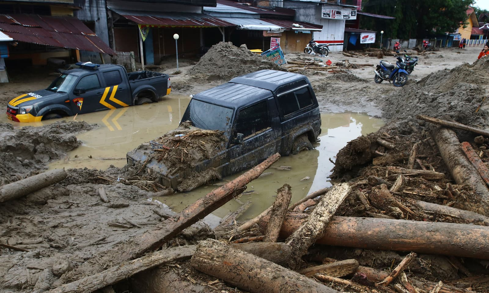 انڈونیشیا کے صوبے سلاسیوی کے علاقے مسامبا میں بارش اور سیلاب کے سبب گاڑیاں کیچڑ میں دھنسی ہوئی ہیں— فوٹو: اے پی