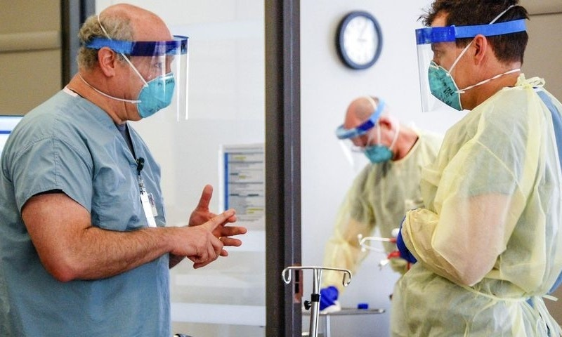 Dr Michael Saag, left, speaks with an unidentified coworker in Birmingham, Alabama, July 10, 2020. Saag survived Covid-19 and now treats patients with the disease. — Amanda Chambers/University of Alabama at Birmingham via AP
