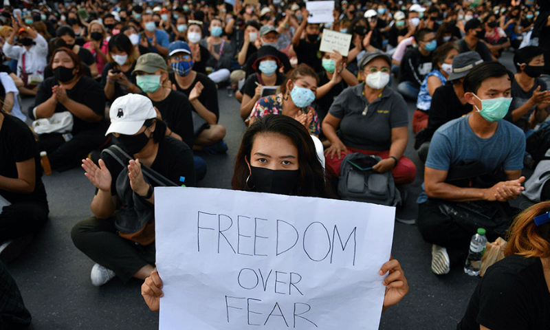 A protester holds a sign during a protest demanding the resignation of the government, in Bangkok on Saturday. — AFP