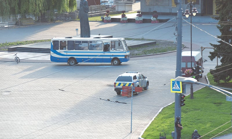 Policemen (bottom right) take up positions during an operation to rescue passengers of an intercity bus who were taken hostage by an armed man in the Ukrainian city of Lutsk on Tuesday.—AFP