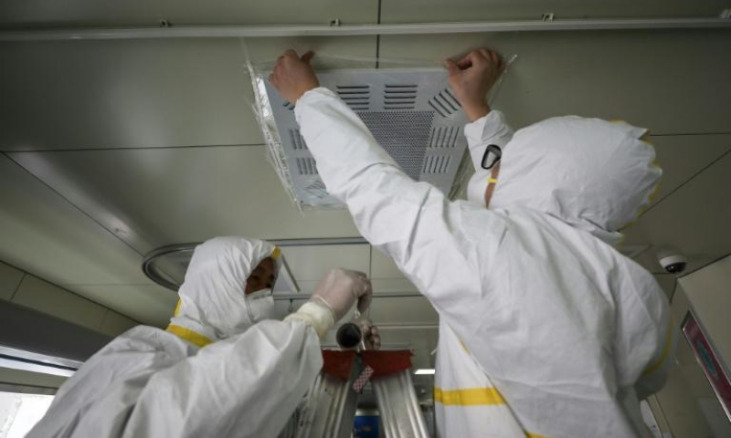 Hospital employees in Wuhan, China seal an airvent to prevent possible airborne transmission of the new coronavirus. — AFP/File