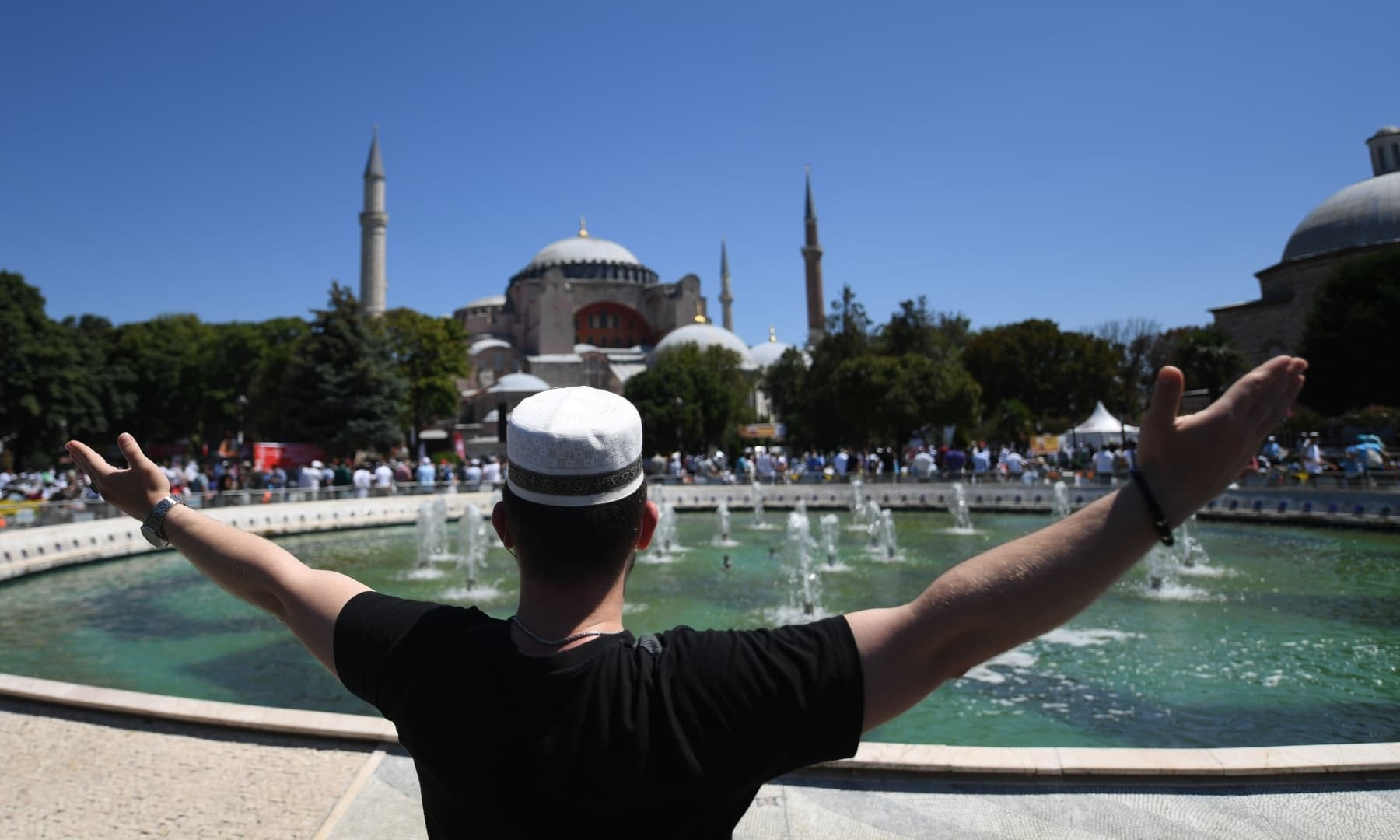 A man raises his arms as people gather outside Hagia Sophia in Istanbul to attend the Friday prayer. — AFP