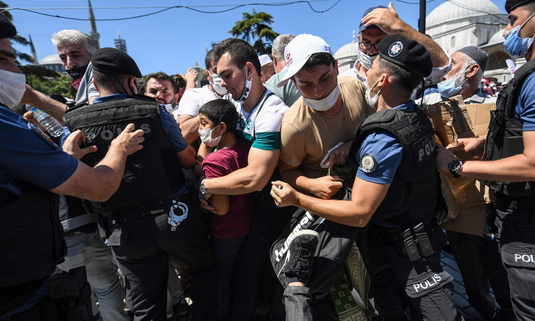 Turkish police scuffle with a small group of faithful trying to enter the overcrowded plaza of the historic Sultanahmet district of Istanbul on Friday as thousands of people gather outside Hagia Sophia to perform the Friday prayer. — AFP