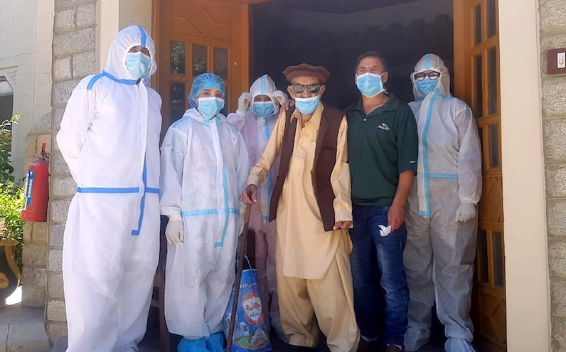 Abdul Alim, 103, stands with his son Suhail Aziz and staff members wearing personal protective equipment (PPE) in this group photograph taken after he recovered from Covid-19 and was discharged from the Aga Khan Health Services Emergency Response Centre in Booni, Chitral. — Photo provided by Reuters