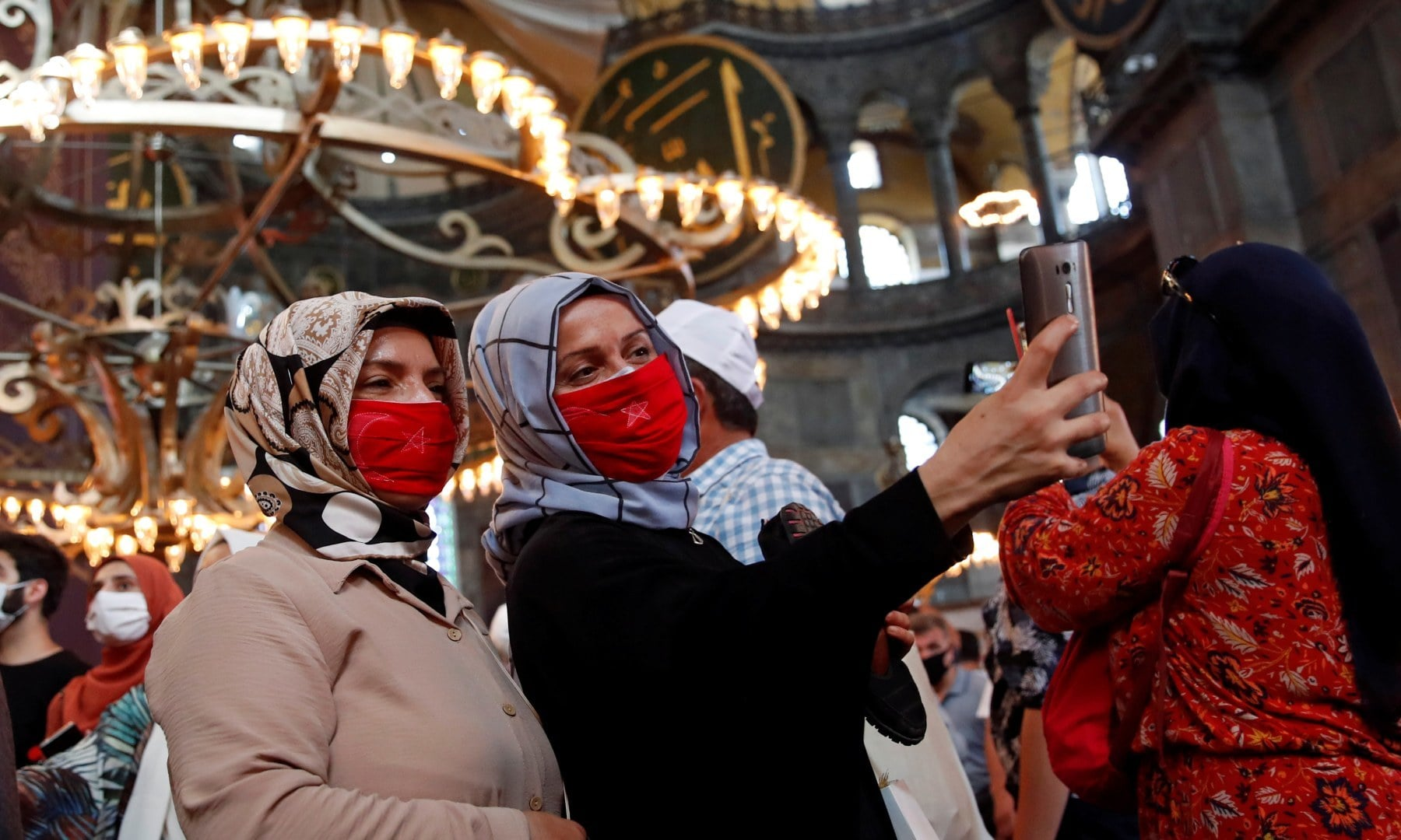 Women take a picture as they attend afternoon prayers and visit Hagia Sophia Grand Mosque. — Reuters