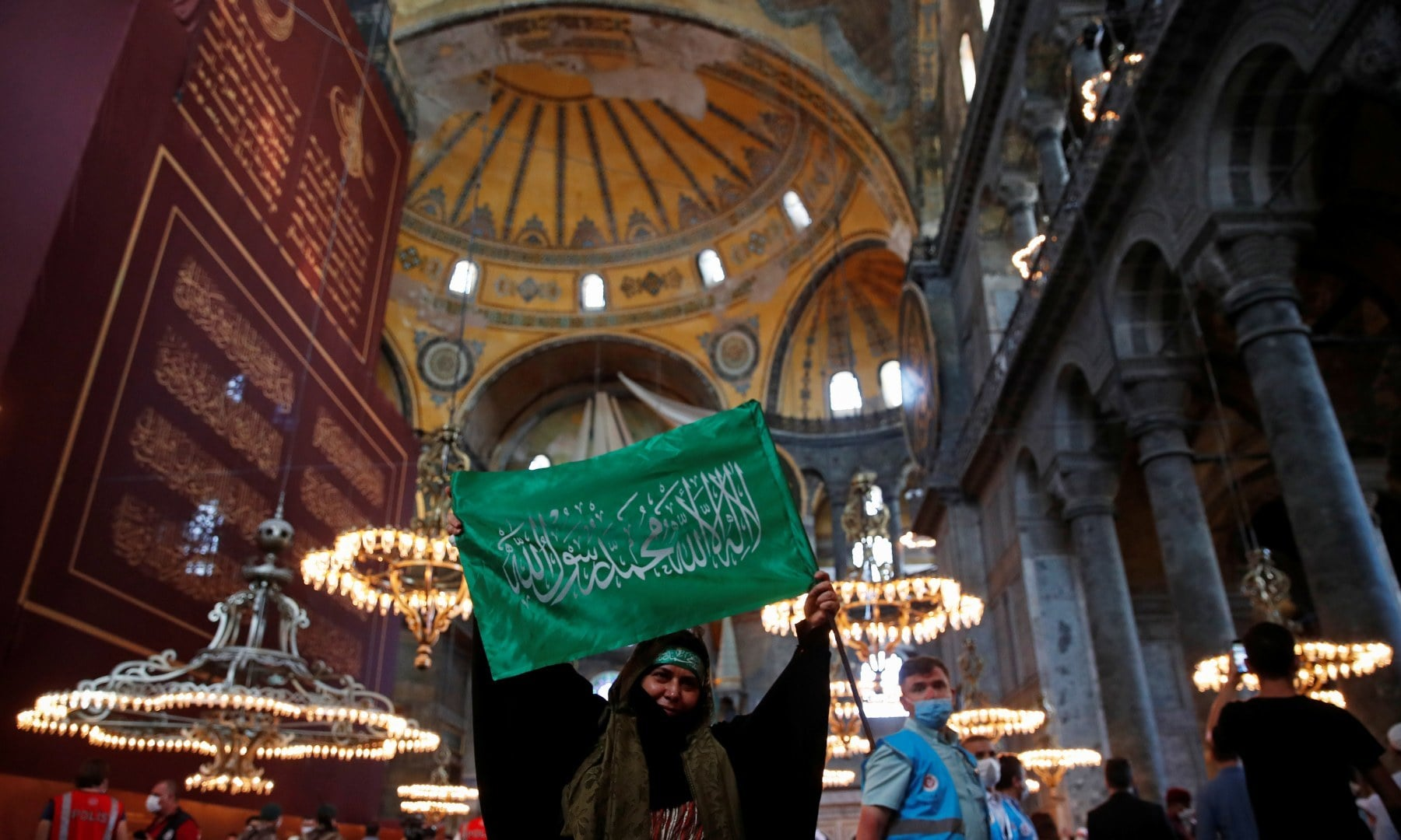 A woman holds a flag as she attends afternoon prayers and visits Hagia Sophia Grand Mosque. — Reuters