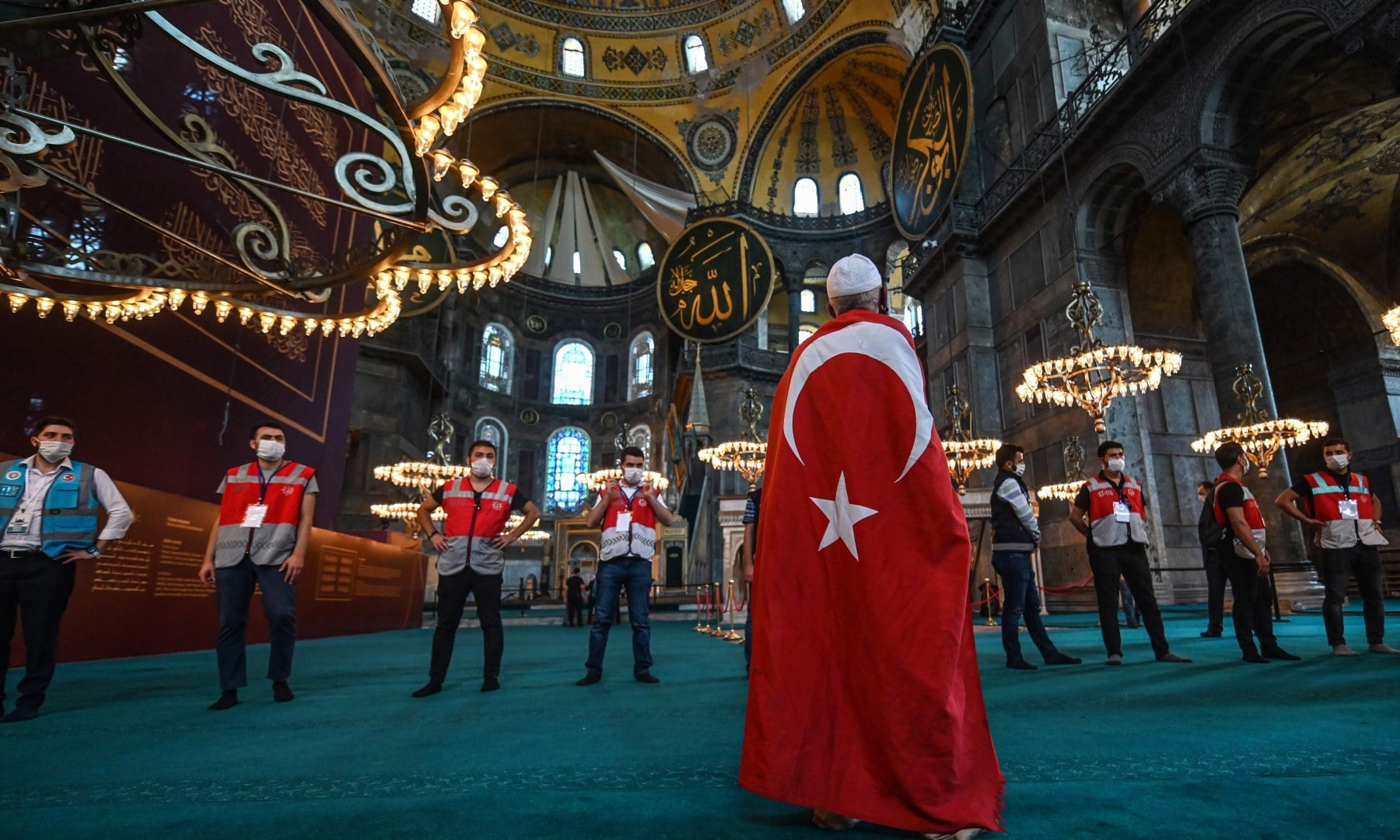 A man wrapped in a Turkish national flag visits the Hagia Sophia in Istanbul. — AFP