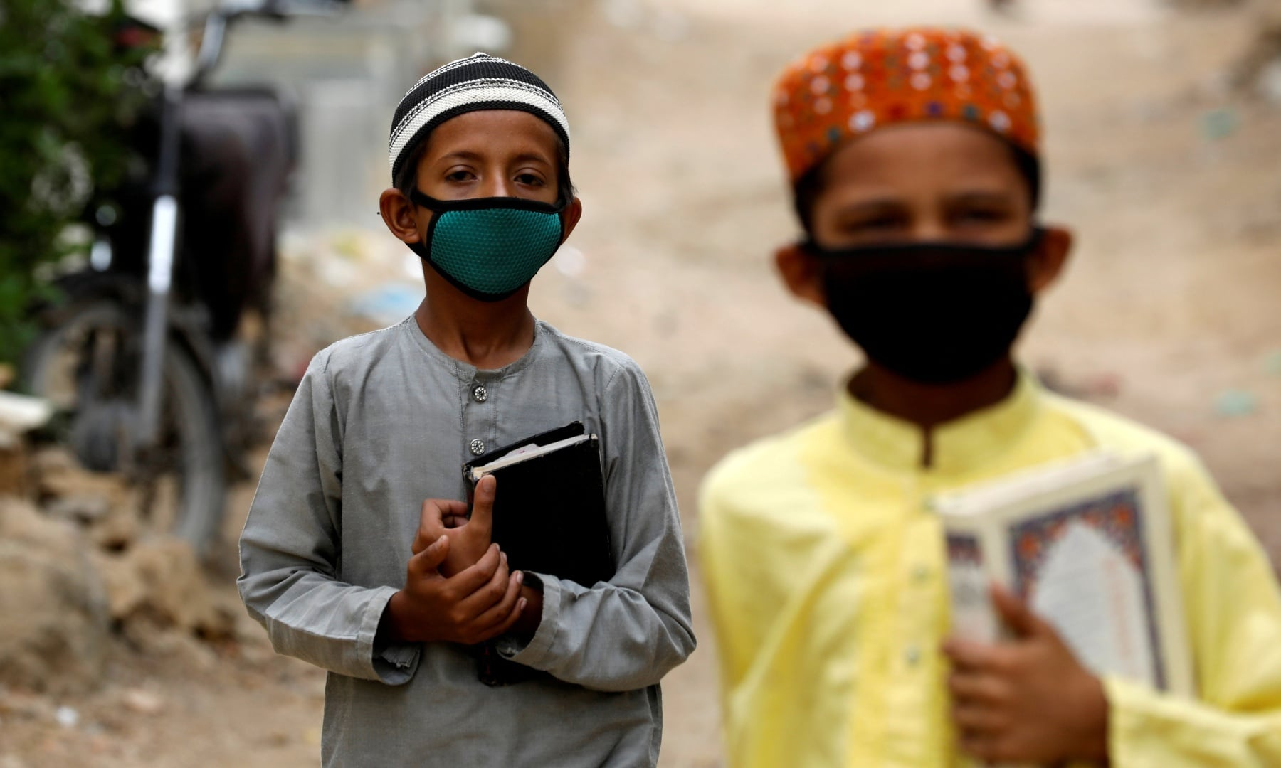 Boys wear protective masks as they head to a madressah during an anti-polio campaign in Karachi, July 20. — Reuters