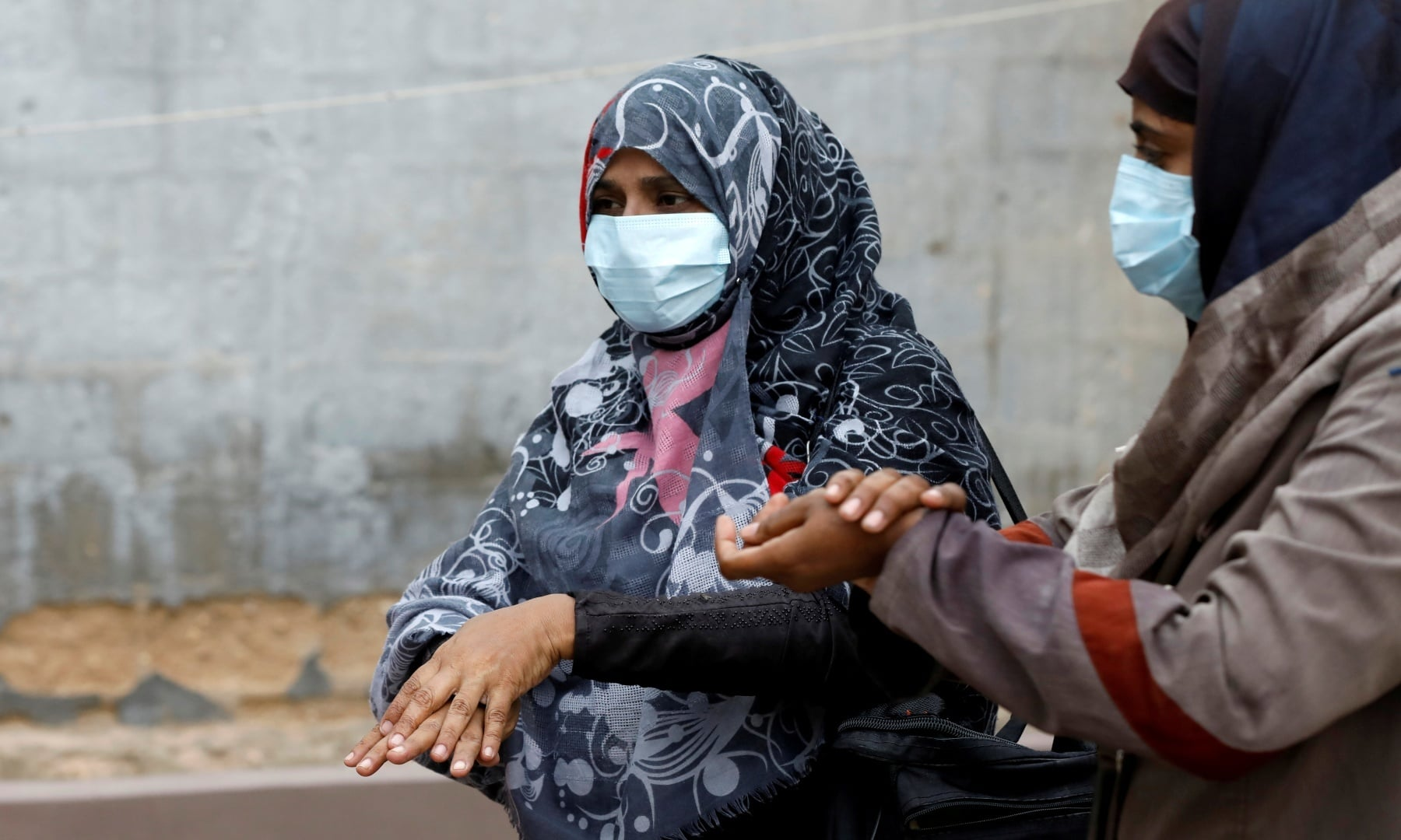 Vaccinators wear protective masks as they sanitise their hands before administering polio vaccine drops, during an anti-polio campaign in Karachi. — Reuters