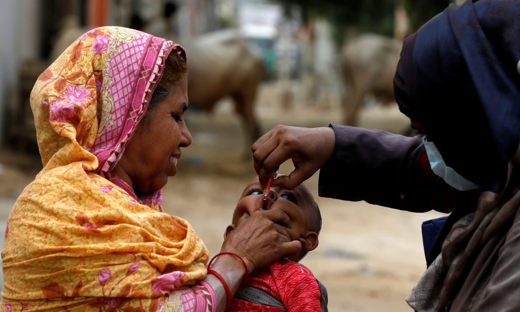 A boy receives polio vaccine drops in Karachi, July 20. — Reuters