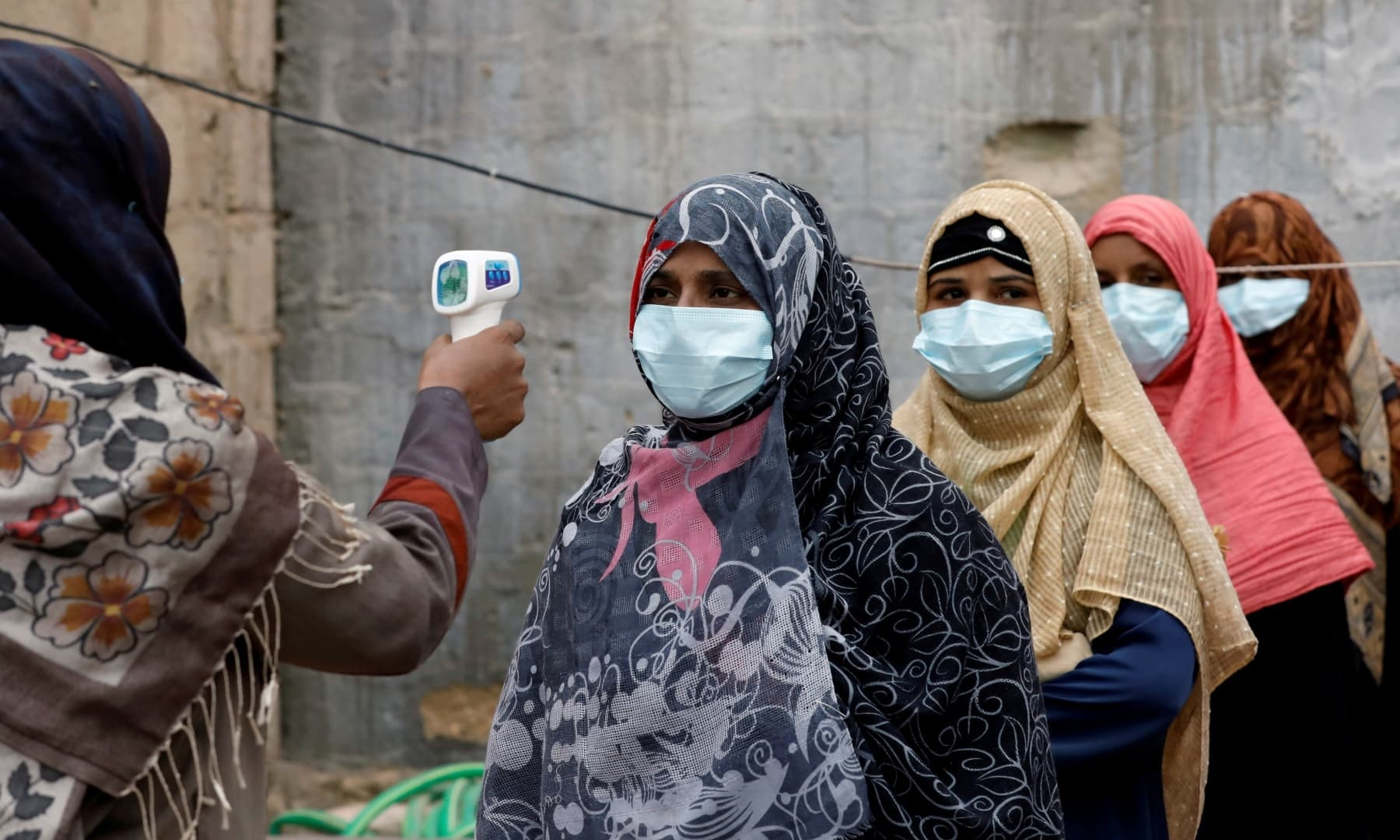 Vaccinators wear protective masks as they get their temperature checked, during an anti-polio campaign, in a low-income neighbourhood in Karachi, July 20. — Reuters