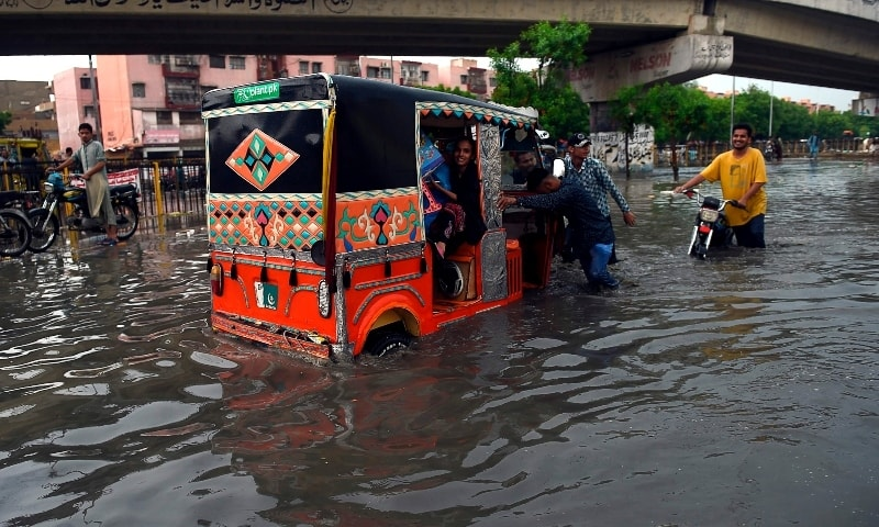 People wade through a flooded street after heavy monsoon rains in Karachi on July 26.  — AFP