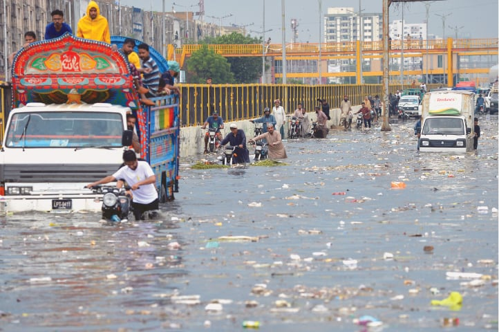 KARACHI: People wade through a flooded road after heavy monsoon rains in the city on Sunday. The downpour left five people dead and played havoc with the ill-maintained civic infrastructure as well as K-Electric's system, causing hours-long power breakdowns in various localities.—AFP