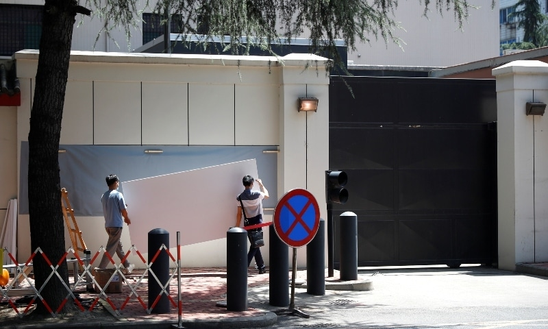 Workers carry a white screen to put it up and cover the signage outside the former US Consulate General in Chengdu on July 27. — Reuters