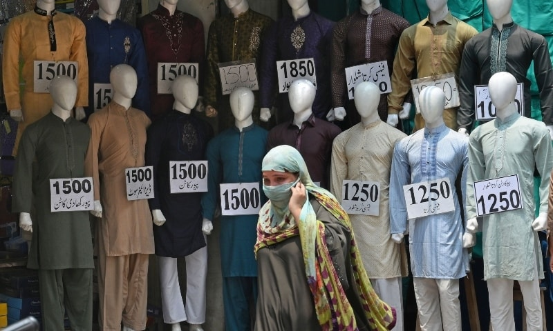 A woman walks past mannequins kept on display outside a cloth shop at a market in Lahore on July 27.  — AFP