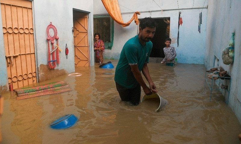 A resident tries to remove water from his house after heavy monsoon rains in Karachi on Monday. — AFP