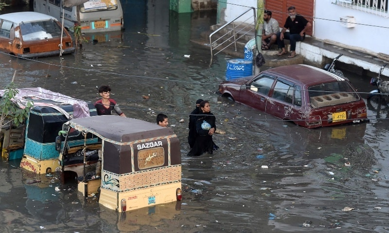 People wade through a flooded street after heavy monsoon rains in Karachi on July 27. — AFP