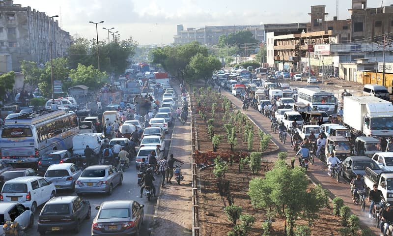PEOPLE suffered prolonged traffic jams on various roads, as here at Shafiq Mor, during and after the rain on Monday.—Shakil Adil / White Star