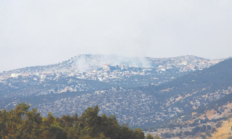 "BEIRUT: A picture taken from the Israeli side of the ""blue line"", which separates Israel and Lebanon, shows smoke billowing above the Shebaa village in southern Lebanon. — AFP"