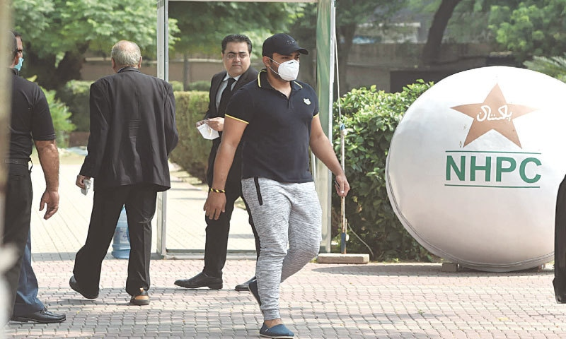 LAHORE: Batsman Umar Akmal (front) arrives with his lawyer at the Pakistan Cricket Board offices on Wednesday.—M. Arif/White Star