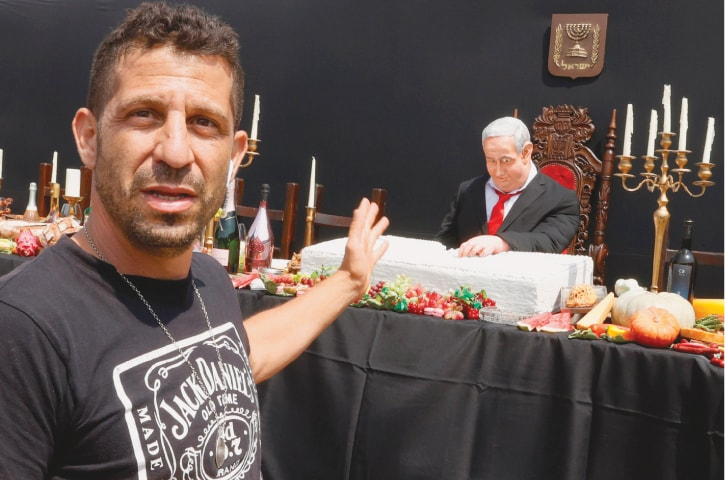 """TEL AVIV: Artist Itay Zalait shows his protest art installation depicting Israeli Prime Minister Benjamin Netanyahu sitting on a table for the """"Last Supper"""".—AFP"""