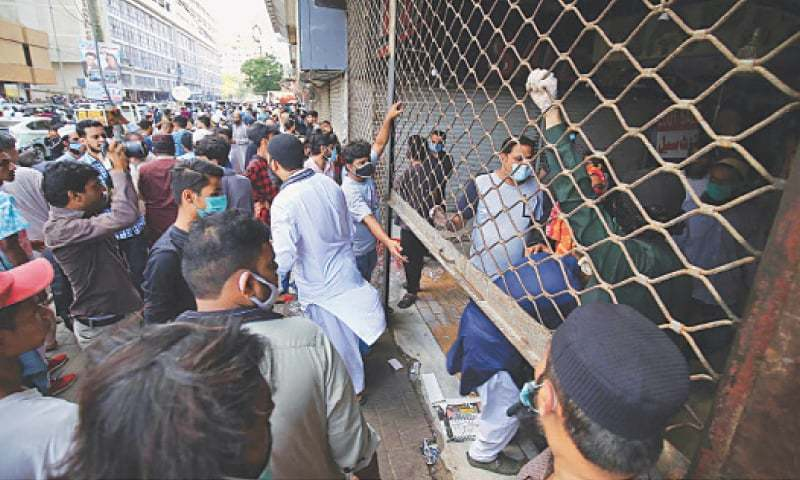 Scores of traders of different bazaars of Clock Tower staged a protest demonstration and refused to accept the lockdown citing financial hardships. — INP/File