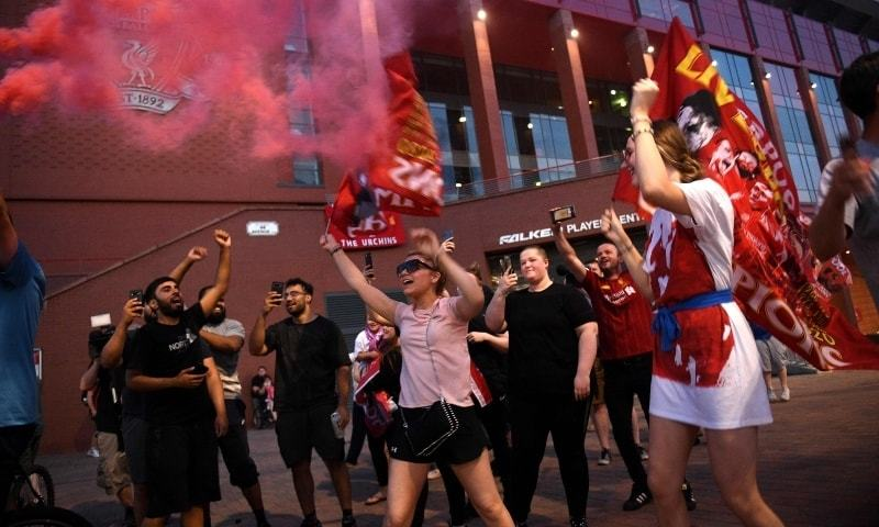 Fans celebrate Liverpool winning the championship title of the English Premier League outside Anfield stadium in Liverpool, north west England on June 25. — AFP/File
