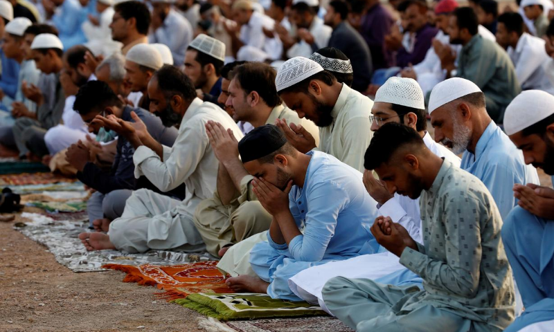 Muslims attend Eidul Azha prayers at a playground in Karachi. — Reuters