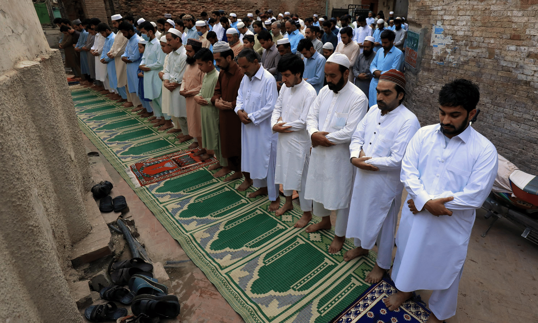 Muslims attend prayers at a street during celebration of Eidul Azha in Peshawar. — Reuters