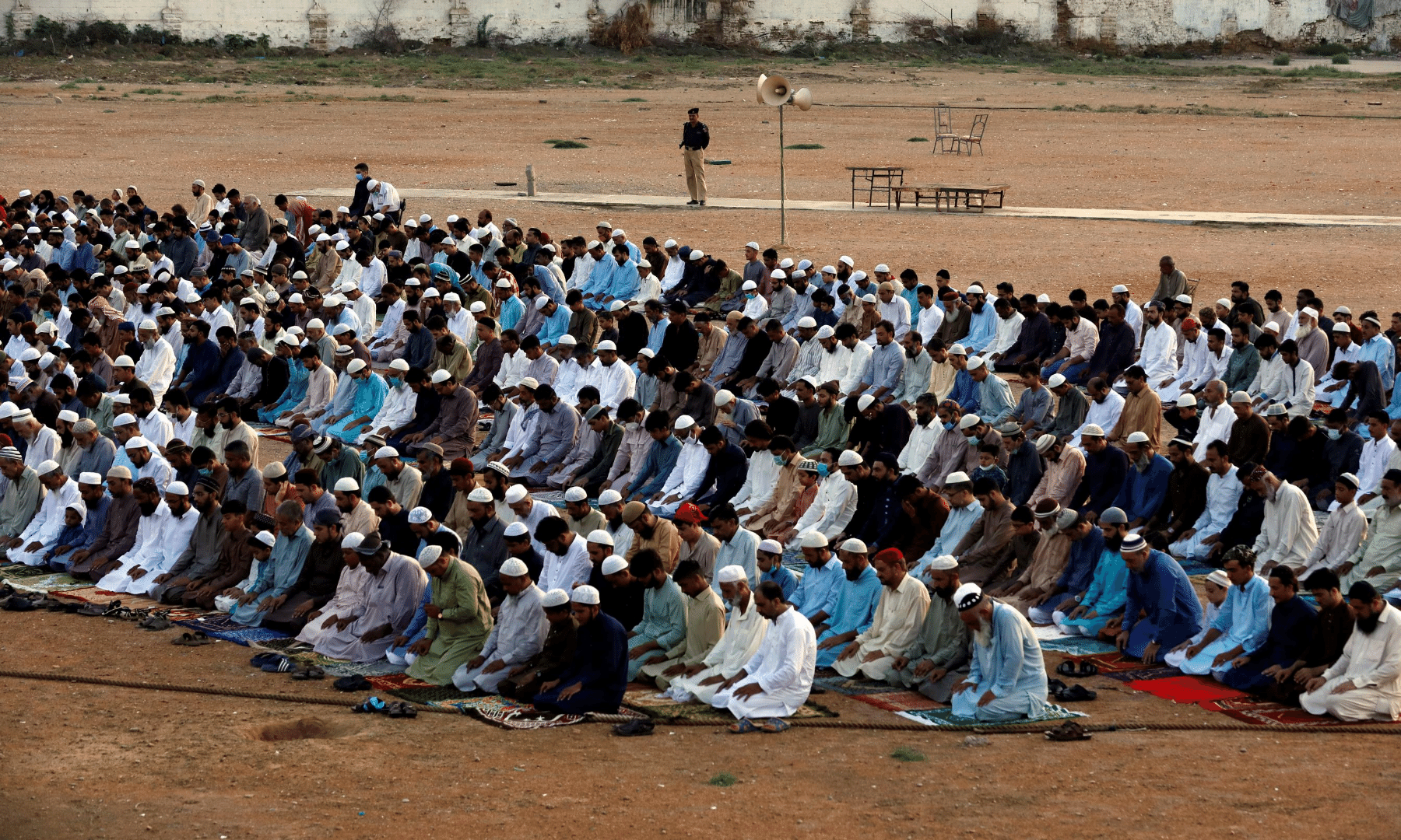 A police officer stands guard as Muslims attend Eidul Azha prayers at a playground in Karachi. — Reuters