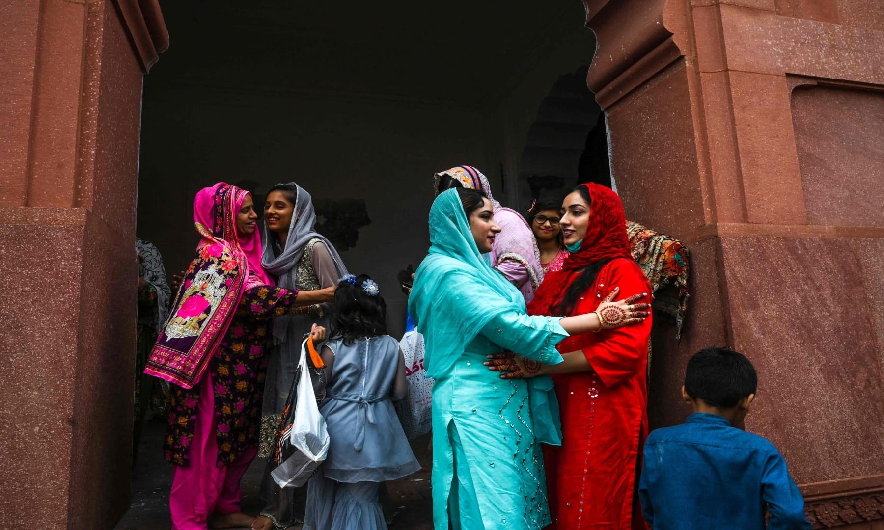 People embrace each other after offering prayers at the Badshahi mosque in Lahore. — AFP