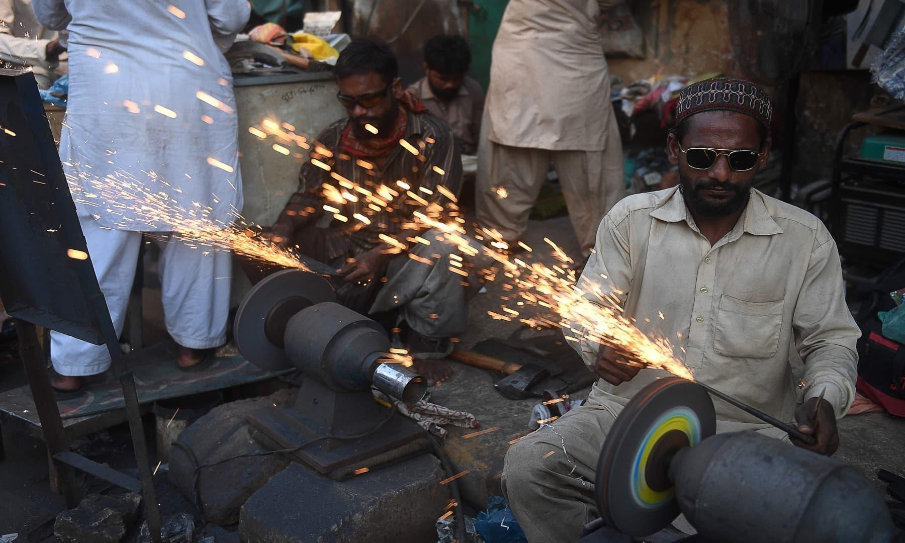 Men sharpen knives at a shop on the eve of Eidul Azha in Karachi on July 31, 2020. — AFP