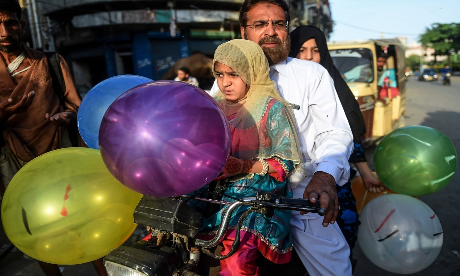 Children hold balloons after offering prayers with their father (C) in Karachi. — AFP