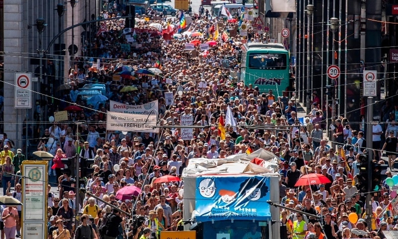 "Thousands of demonstrators march down the Friedrichstrasse street as they take part in a demonstration by the initiative ""Querdenken-711"" with the slogan ""the end of the pandemic-the day of freedom"" to protest against the current measures to curb the spread of the Coronavirus, in Berlin, on August 1. — AFP"