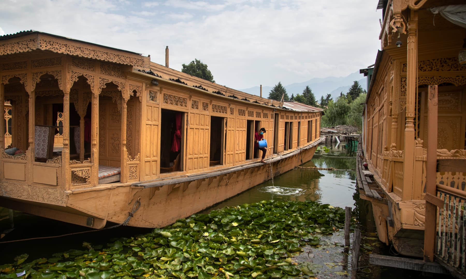 Kashmiri man Illiyas Ahmad cleans an unoccupied houseboat at Nigeen Lake during lockdown to stop the spread of the coronavirus in Srinagar, July 16. — AP