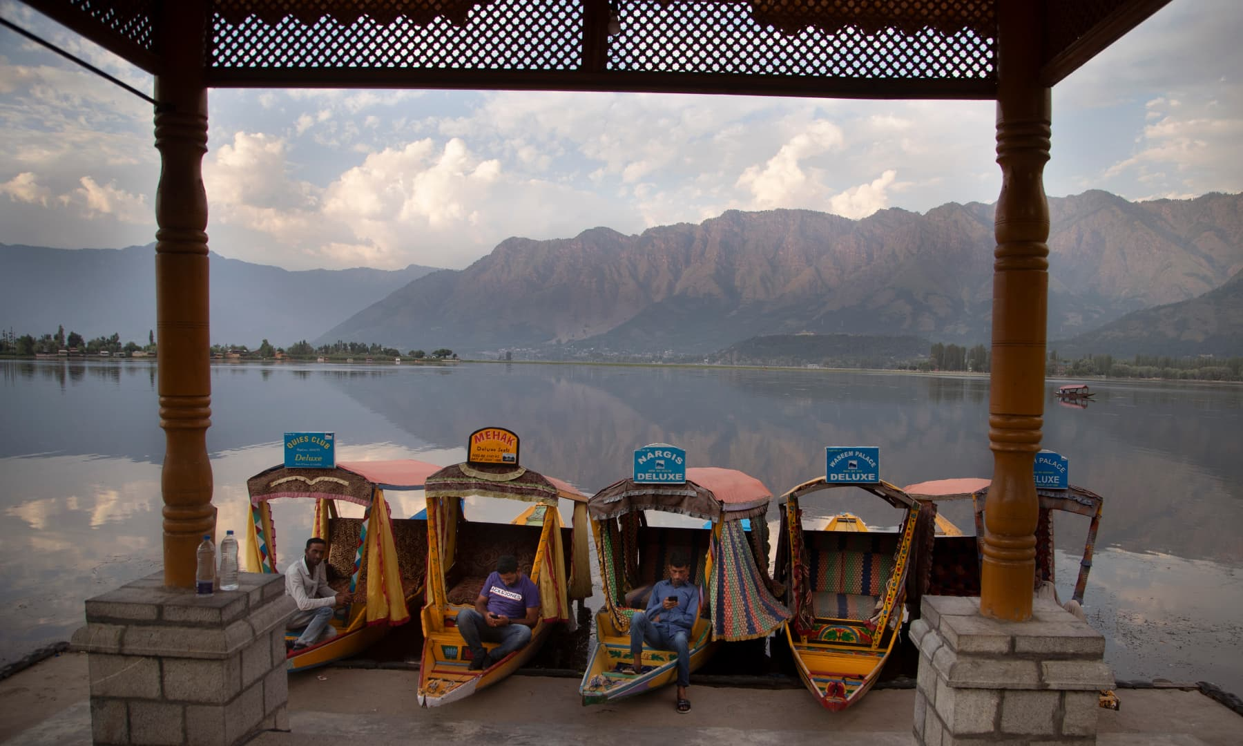 Kashmiri boatmen rest as they wait for customers on the deserted banks of the Dal Lake in Srinagar, July 20. — AP