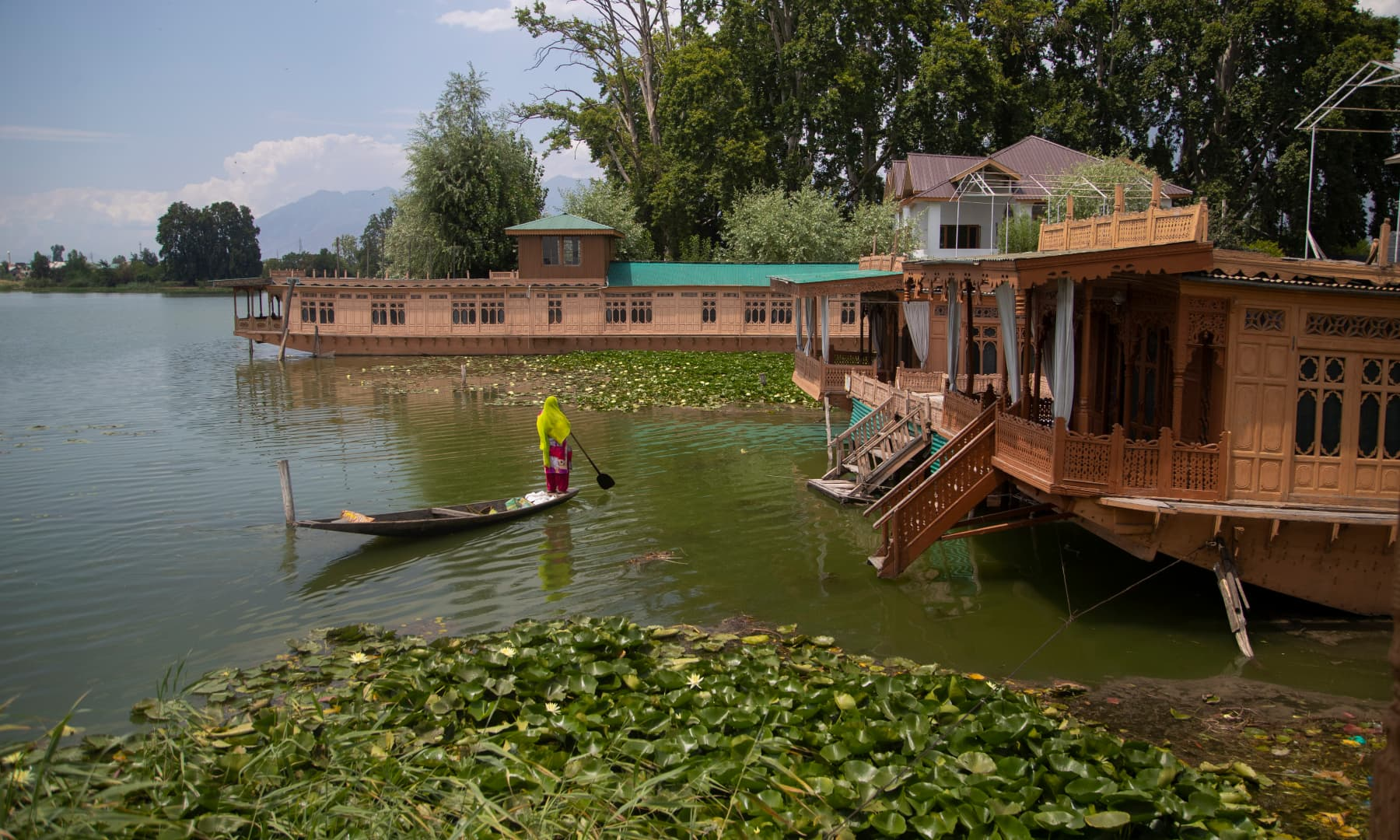 A Kashmiri woman rows her boat near unoccupied houseboats at Nigeen Lake in Srinagar, July 16. — AP