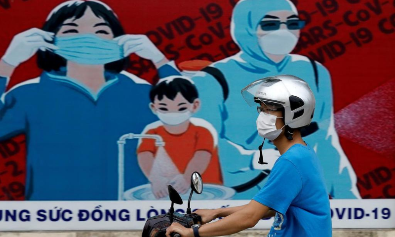 A man wears a protective mask as he drives past a banner promoting prevention against the coronavirus in Hanoi, Vietnam. — Reuters/File