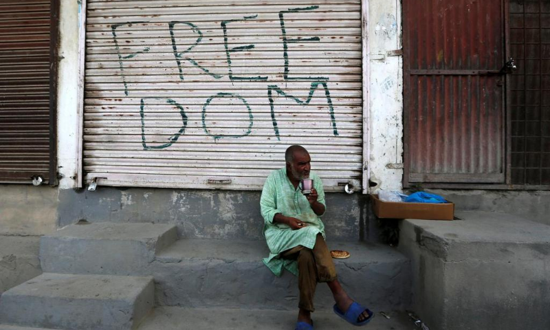 A Kashmiri man drinks tea in front of a closed shop painted with graffiti in Anchar neighbourhood in Srinagar on July 28. — Reuters/File