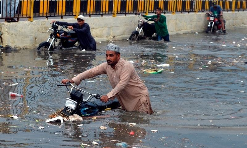 People wade through a flooded street after heavy monsoon rains in Karachi on July 26.  — AFP/File