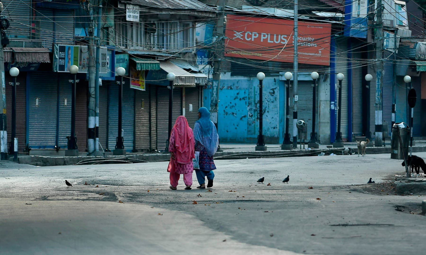 Women walk before a curfew in Srinagar on August 4, 2020. - A curfew has been imposed across Indian Kashmir just two days before the first anniversary of New Delhi's abolition of the restive region's semi-autonomy, officials said late August 3, citing intelligence reports of looming protests. (Photo by TAUSEEF MUSTAFA / AFP)