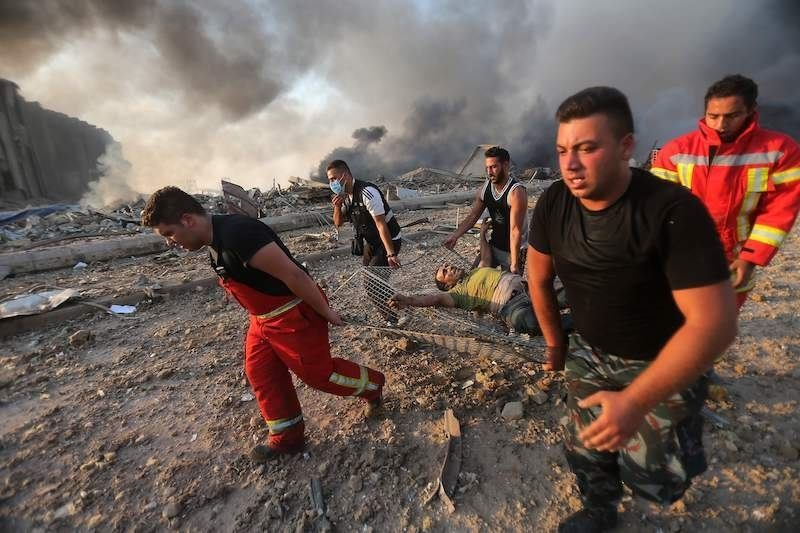 Firefighters evacuate a wounded man from the scene of an explosion at the port in Beirut on August 4. — AFP