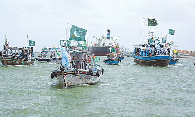 Fishermen and PTI supporters take out a boat rally in solidarity with Kashmiris on Tuesday.—APP