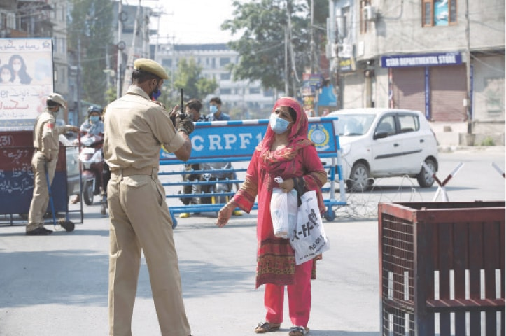 SRINAGAR: A woman requests a police officer to let her cross a street during curfew here on Tuesday.—AP