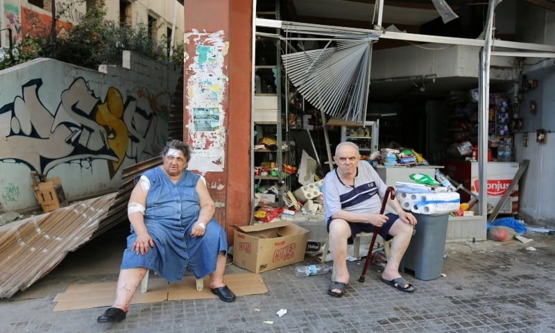 A woman, who was injured in Tuesday's blast, sits next to her husband outside their damaged grocery store in Beirut on August 5. — Reuters