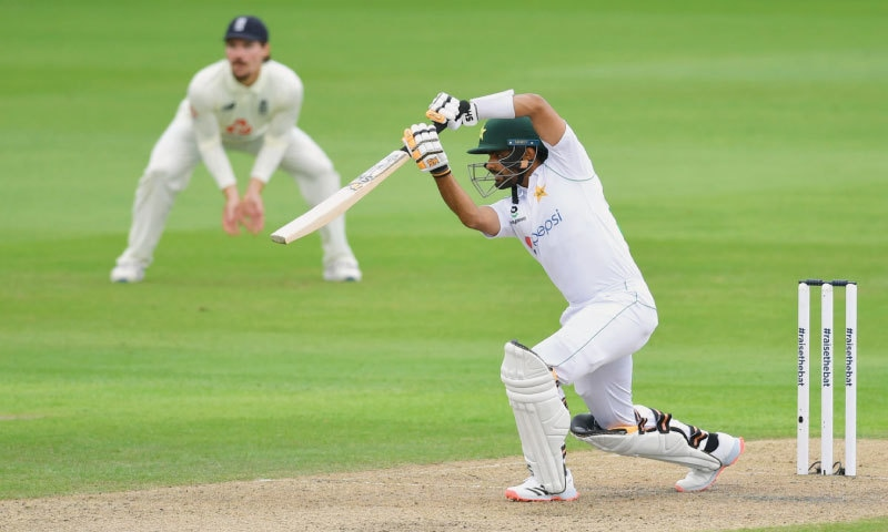 Babar Azam drives elegantly during his fluent, unbeaten half-century on the first day.—AFP