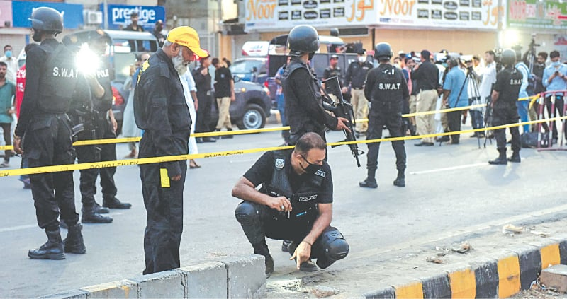 POLICE officers scour the crime scene on University Road for evidence after the blast on Wednesday evening.—Fahim Siddiqi/White Star