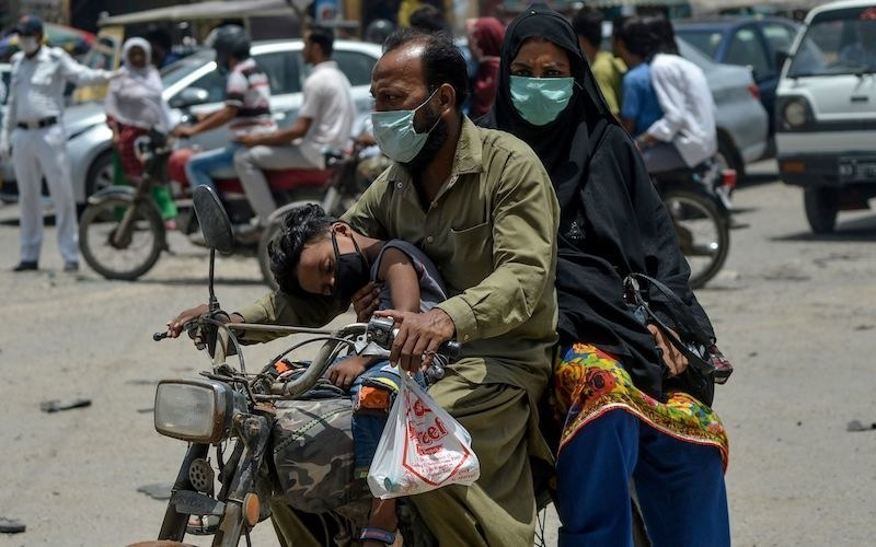 In this picture taken on July 23, 2020, a family wearing face masks ride a motorbike on a street in Karachi. — AFP/File