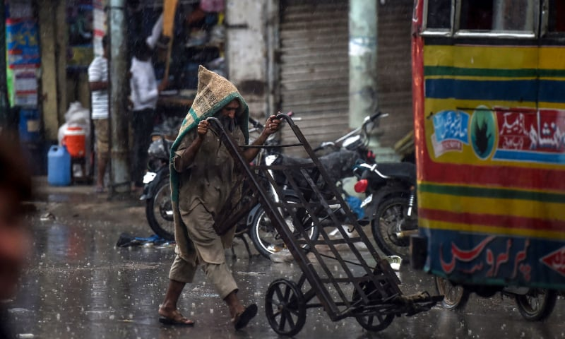 A labourer covers himself as he pushes a cart on a street under the rain in Karachi on August 6. — AFP